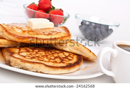 stack of pancakes with  butter and slathered with syrup