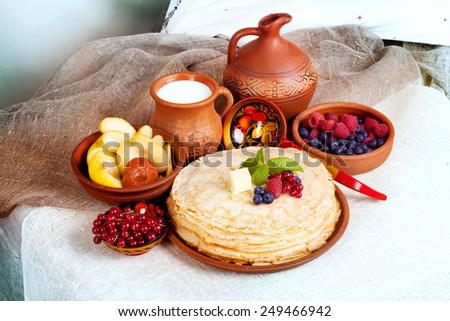 stack of pancakes with butter, berries and mint in a still life with pottery and milk - stock photo