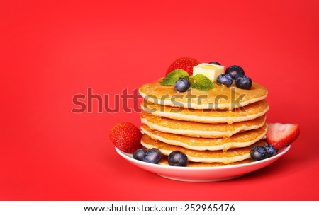 Stack of pancakes with fresh blueberry and strawberry on red background