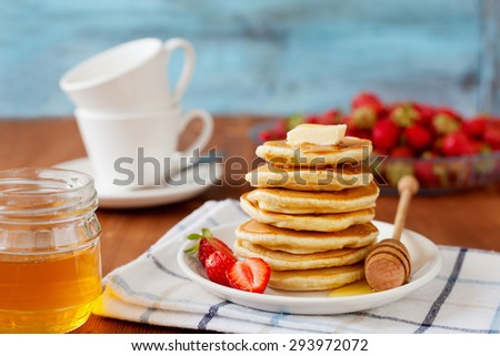 Stack of pancakes with honey syrup, butter and strawberry in a white plate on a wooden rustic table, selective focus - stock photo
