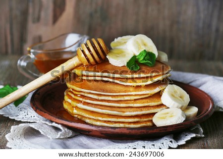 Stack of pancakes with mint, honey and slices of banana on rustic wooden background - stock photo