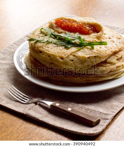 stack of pancakes with red caviar on a white plate, fork, knife