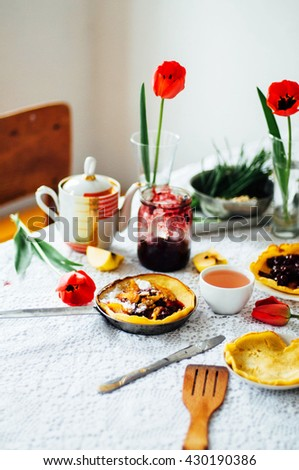 Stack of pancakes with red cherry jam. Pancakes withcherry jam. pancakes or fritters served with cherry jam, delicious dessert for breakfast , rustic style. Hot pancakes with cherry jam on pan. - stock photo