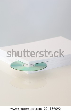 Stack of paper with CD emerging from the corner - stock photo