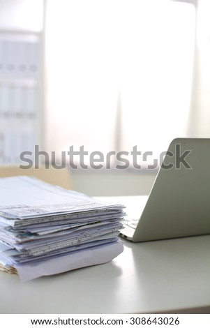 Stack of papers and glasses lying on table desaturated - stock photo