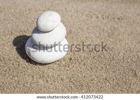 stack of pebble stones on balance on sand - stock photo