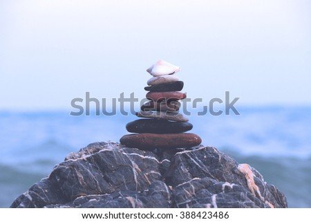 Stack of pebbles zen stone on the beach, blue filter effect - stock photo