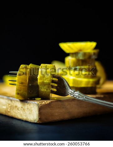 Stack of pickle slices behind an antique fork with more pickles on a rustic wooden cutting board.  - stock photo