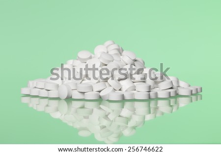 Stack of pills towards green background - stock photo