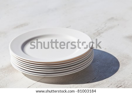 Stack of plates and shadow, on dining table - stock photo