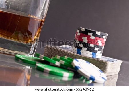 Stack of Poker Chips on Card Deck with Gambling Assets - stock photo