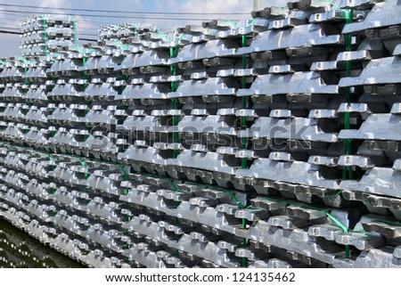 Stack of raw Aluminium Ingot & reflextion on outdoor warehouse - stock photo