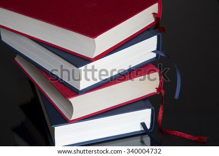 Stack of red and blue books on black background