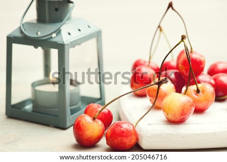 Stack of red and yellow cherries on white wooden background with lit lantern. Sepia toned image - stock photo