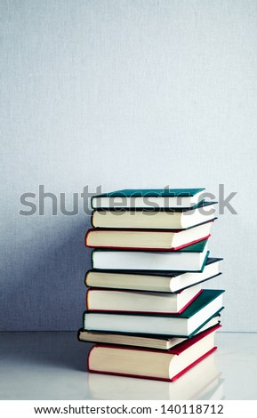 Stack of red, green and black books on white reflective surface