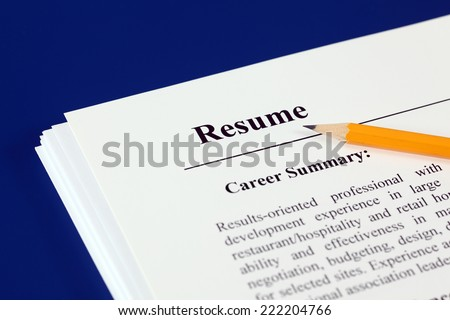 Stack of resumes with pencil on a blue background. - stock photo