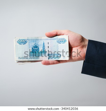 Stack of Russian money in hand on a gray background. Business and Finance. 1000 rubles.