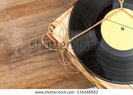 Stack of scratched dusty old vinyl records tied with rope on wooden table - stock photo