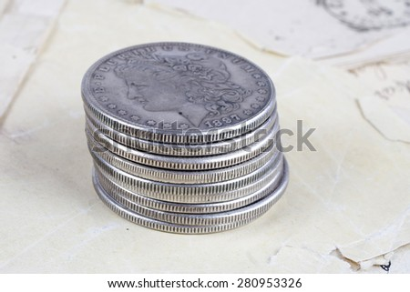 stack of silver dollar coins on old paper