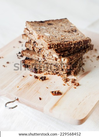 Stack of Sliced Unleavened Bread from a Rough Grinding with Muesli, Nuts and Sesame Seeds on a chopping board - stock photo