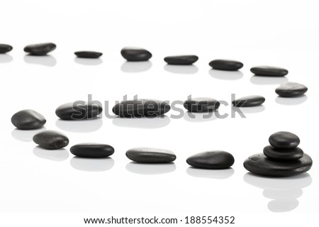 Stack of spa hot stones isolated on white background - stock photo