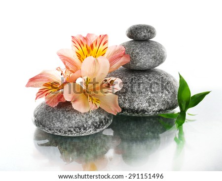 Stack of spa stones with flower isolated on white - stock photo