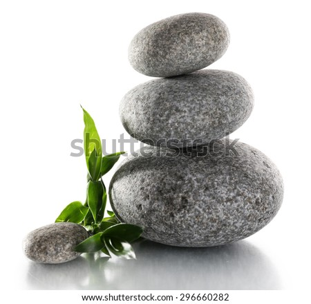 Stack of spa stones with green leaves isolated on white