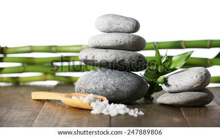 Stack of spa stones with spoon of sea salt on wooden surface isolated on white - stock photo