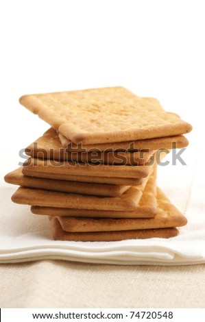 Stack of square crackers on beige linen napkin.