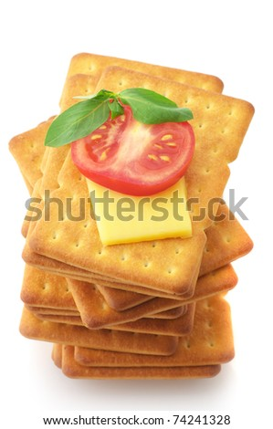 Stack of square crackers with slices of cheese, tomato and basil isolated on white background. - stock photo