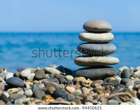 Stack of stones on beach, sea and sky - stock photo