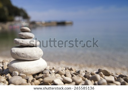 Stack of stones on sandy sea beach against dramatic background, Zen, Feng shui concept, selective focus - stock photo