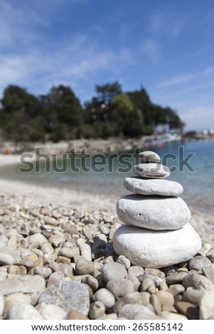 Stack of stones on sandy sea beach against dramatic background, Zen, Feng shui concept, selective focus. - stock photo