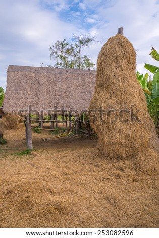 stack of straw or hay bales in a rural landscape. - stock photo