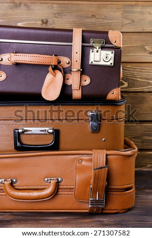 Stack of suitcases on wooden background - stock photo