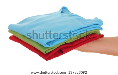 stack of t-shirt on women hand, over white background - stock photo