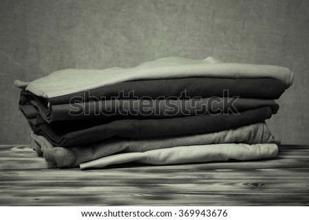 Stack of T-shirts on wooden table opposite a defocused burlap background. Toned.