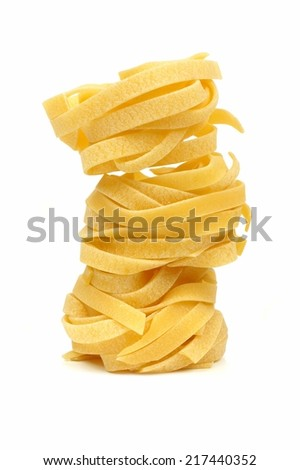 Stack of tagliatelle pasta nests over a white background - stock photo