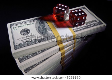 Stack of Ten Thousand Dollar Piles of One Hundred Dollar Bills & Dice on a black background.