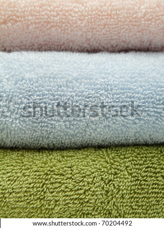 Stack of three bath towels of different colors - stock photo