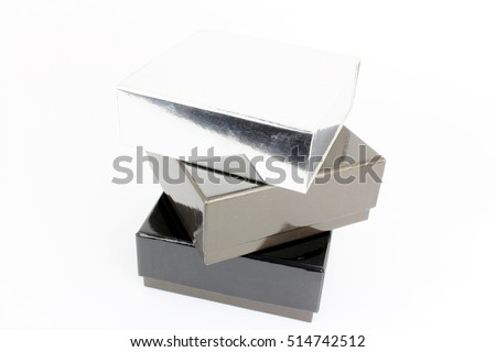 Stack of three books, vertically. silver, gray and black with white background.