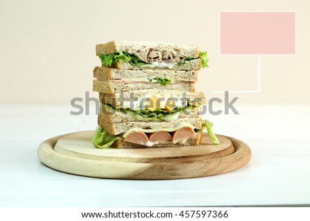 Stack of three delicious toasted sandwiches with different fillings including tuna, ham,cheese, fried egg, sausage , all garnished with herb and salad ingredient and text box for put in word. - stock photo