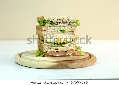 Stack of three delicious toasted sandwiches with different fillings including tuna, ham,cheese, fried egg, sausage , all garnished with herb and salad ingredients,close up view - stock photo