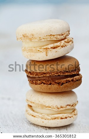 Stack of three french macarons over a rustic wooden background. Extreme shallow depth of field with selective focus. - stock photo