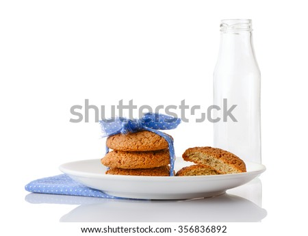 Stack of three homemade oatmeal cookies tied with blue ribbon in small white polka dots and halves of cookies on white plate on napkin and empty milk bottle, isolated on white background - stock photo
