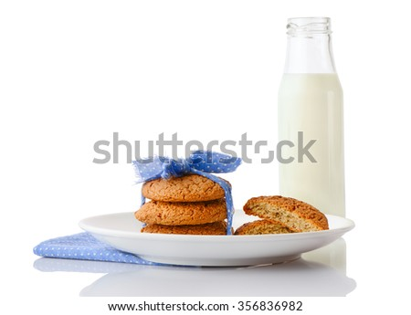 Stack of three homemade oatmeal cookies tied with blue ribbon in small white polka dots and halves of cookies on white ceramic plate on blue napkin and bottle of milk, isolated on white background - stock photo