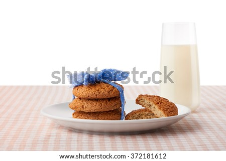 Stack of three homemade oatmeal cookies tied with blue ribbon in small white polka dots and halves of cookies on white plate and glass of milk on checkered tablecloth, isolated on white background - stock photo