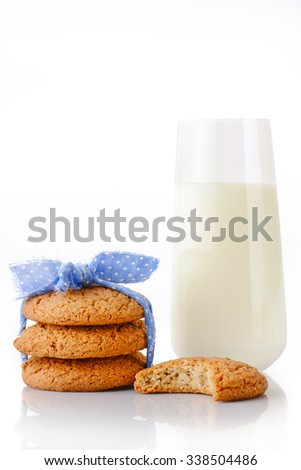 Stack of three homemade oatmeal cookies tied with blue ribbon in small white polka dots, bitten cookie and glass of milk, isolated on white background