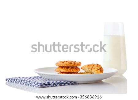Stack of three homemade peanut butter cookies and halves of cookies on white ceramic plate on blue napkin and glass of milk, isolated on white background - stock photo