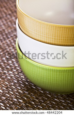Stack of Three Multi-colored Bowls on Placemat - stock photo